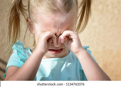 A little girl is crying and rubbing her eyes with her hands. Children's hysteria. A close-up photo.