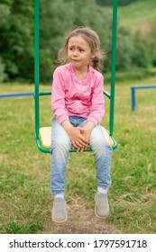 Little girl crying sitting on a swing at the playground