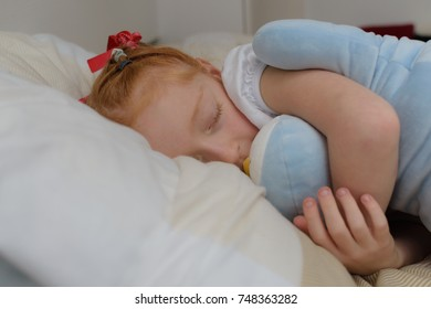 little girl cuddling her soft teddy plush toy whilst asleep on her bed, head on her white and cream pillow.
