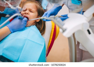 A little girl is curing a tooth from a dentist.