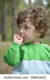 Little girl with a curiosity for someone watches and keeps his finger in his mouth.