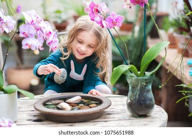 A little girl with curls and a green dress in a winter garden behind an old wooden wooden rustic table with flowering orchids and a tub of water and stones. Children play with stones and orchids