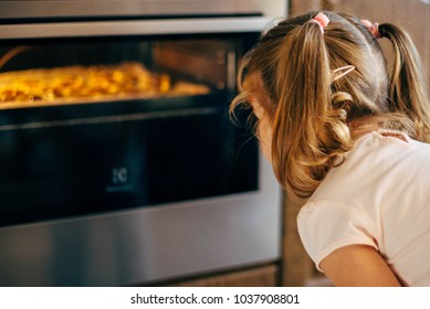 Little girl with a curly blond hair is watching cookies baking in an oven