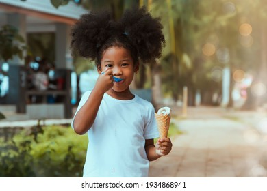 Little girl with curly hair, fluffy, delicious ice cream : Portrait 5-year-old, half-Asian, African girl walks eating ice cream in a garden and enjoys hand-melted milk cream on a hot day in Thailand.