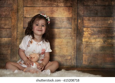 Little girl with curly hair, having fun while posing at the camera