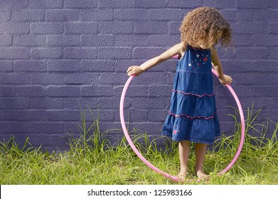Little girl with curly hair standing in front of a blue brick wall looking down at her hula hoop which she is holding