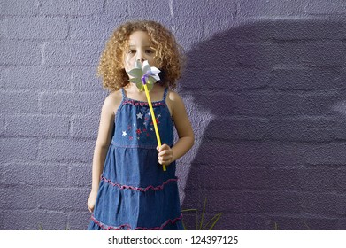 little girl with curly hair, wearing blue dress, blowing a pinwheel, against a purple brick wall