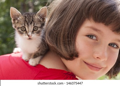 Little girl with cute kitten. Outdoor