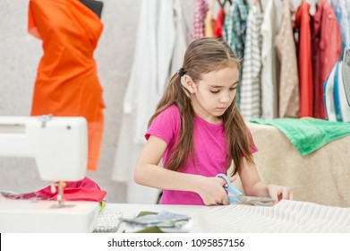 Little girl cuts dress detail with scissors at workplace seamstress