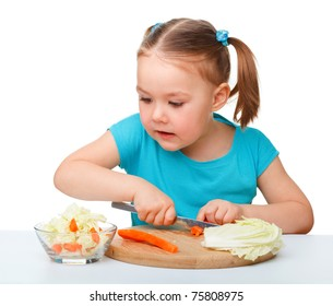 Little girl is cutting carrot for salad using kitchen knife, isolated over white