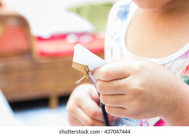 The little girl is cutting color paper. The little girl makes handcraft.