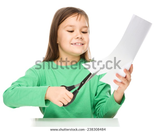 Little girl is cutting paper using scissors while sitting at table, isolated over white