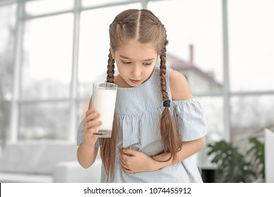 Little girl with dairy allergy holding glass of milk indoors