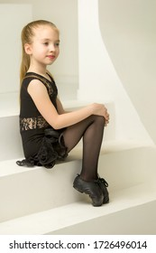 Little girl in a dance costume is sitting on the stairs.