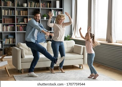 Little girl dancing in living room at home with father and elderly grand mother, funny multi-generational active family fooling around spending weekend time came to visit old granny having fun indoors