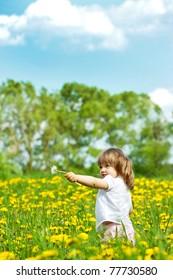 Little girl in a dandelion meadow holding dandelion in the hand