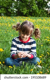 Little girl with dandelion on the green lawn