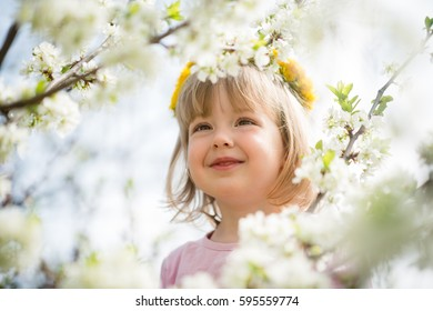 Little girl with dandelion wreath on head enjoys blooming fruit tree flowers