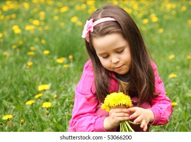 Little girl with dandelions in the meadow