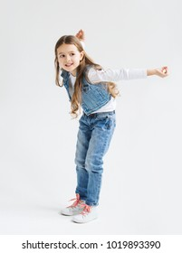 Little girl with dark long hair in jeans and jeans jelly and sneakers  having fun on a white background.