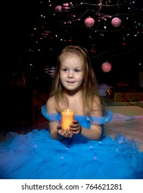 A little girl in a dark room, on Christmas night, with a burning candle in her hands. Concept of a holiday, Christmas, family well-being, Happy childhood.