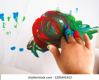Little girl at daycare, creating paint art with fingers on white paper