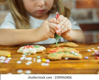 Little girl decorate Christmas cookies for the holiday.