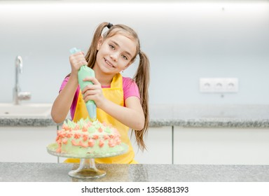 little girl decorating chocolate cake in the kitchen. Empty space for text