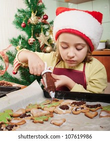 Little girl decorating the christmas cookies
