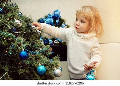 little girl decorating a Christmas tree with blue balls