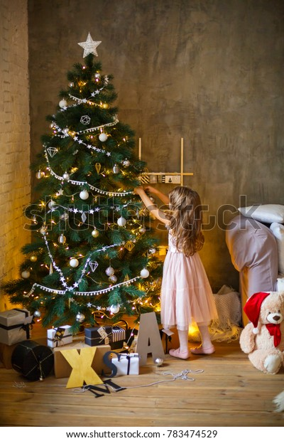 Little girl decorating christmas tree indoor. Christmas. New Year. Holiday. Home. Family vacation