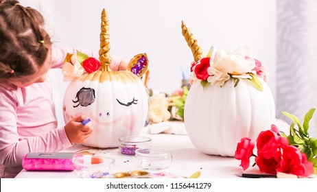 Little girl decorating her craft pumpkin with unicorn theme for Halloween.