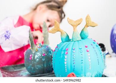 Little girl decorating her Halloween pumpkin with rhinestones.