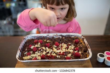 Little girl decorating Mazurek (Polish Easter cake)