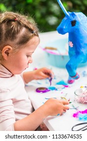 Little girl decorating painted blue paper mache unicorn.