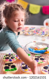 Little girl decorating sugar cookies with royal icing for Dia de los Muertos holiday.