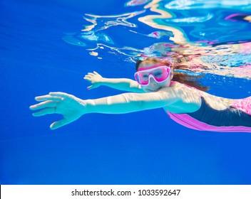 little girl deftly swim underwater in pooll.Underwater photo.