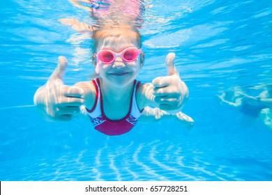 little girl deftly swim underwater in pool