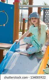 Little girl in denim peaky cap playing