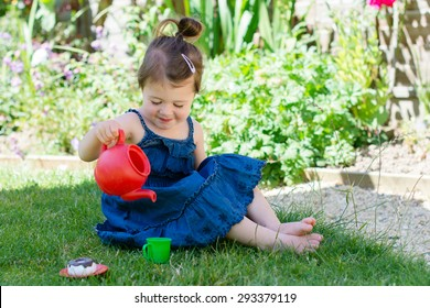 A little girl in a denim sun dress playing with teapot and cup