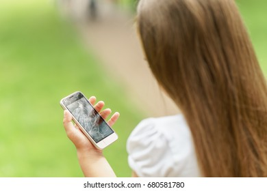 little girl in desperation is holding a phone with a broken screen at day time