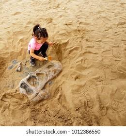 little girl digging sand to find bones