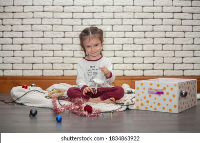A little girl dismantles a box with Christmas decorations. A girl holding a Christmas tree toy in the form of a ballerina. Christmas holidays.