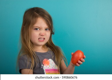 Little girl with displeased expression holding tomato