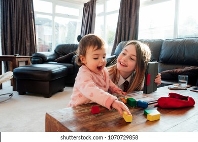 Little girl is distracting her older sister while she is trying to study at home. They are playing with toy blocks together.