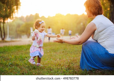 Little girl do her first steps with mother's help