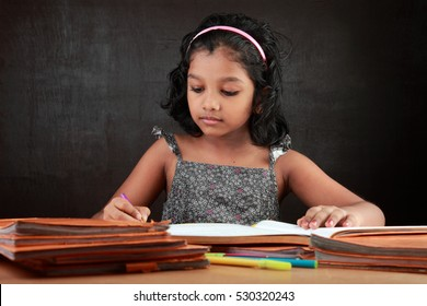 A little girl does her homework in the study room