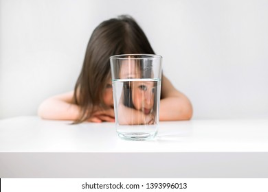 Little girl does not want to drink water. The girl sits at the table upset. The girl is sad because she does not want to drink water. Girl sitting next to a glass of water