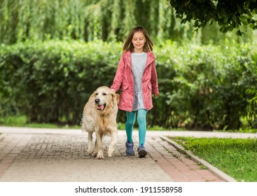 Little girl with dog going along alley