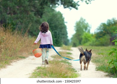 Little girl with dog walking on the sand road